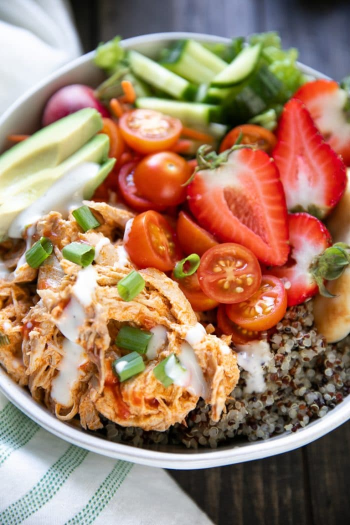 Bowl filled with quinoa, lettuce, shredded buffalo chicken, avocado, and strawberries.