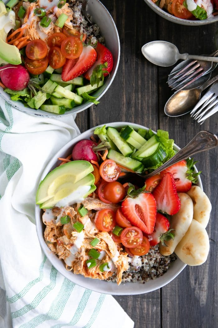 Ready to eat quinoa bowl filled with shredded buffalo chicken, pita bread, salad, tomatoes, avocado, and strawberries