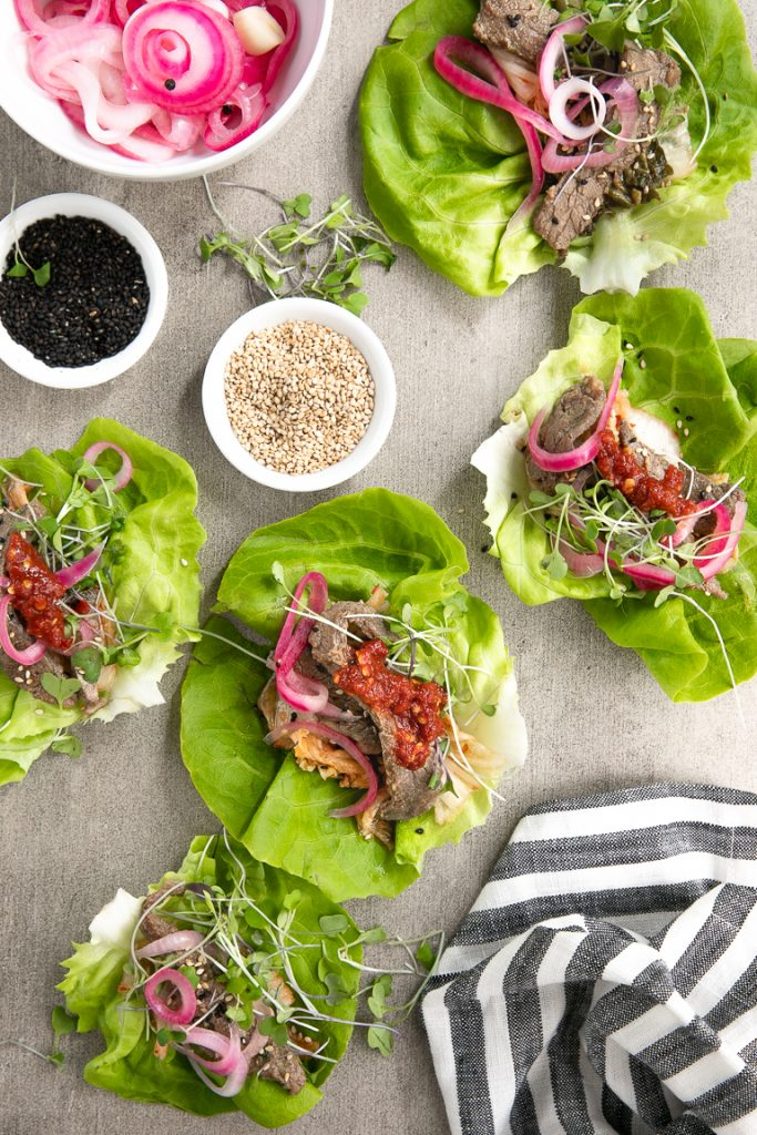 Korean BBQ Beef served with kimchi, pickled red onions, butter lettuce and micro greens