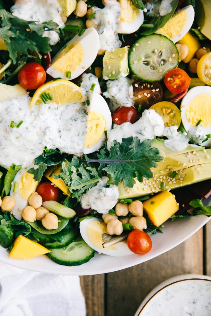 fresh and healthy salad on table filled with tomatoes, kale, mango, avocado