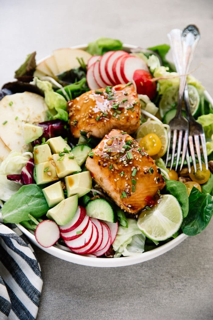 Large white salad bowl filled with apples, avocado, lettuce, tomatoes, radish, and topped with two cooked salmon fillets.