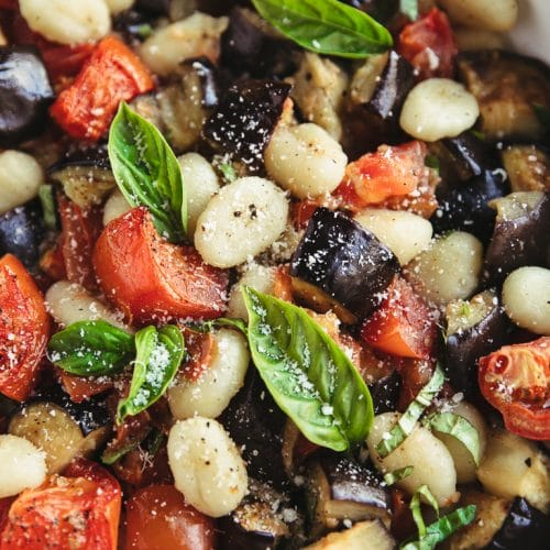 Close up image of a large white nonstick skillet filled with potato gnocchi, roasted tomatoes, eggplant, fresh basil, and parmesan cheese.