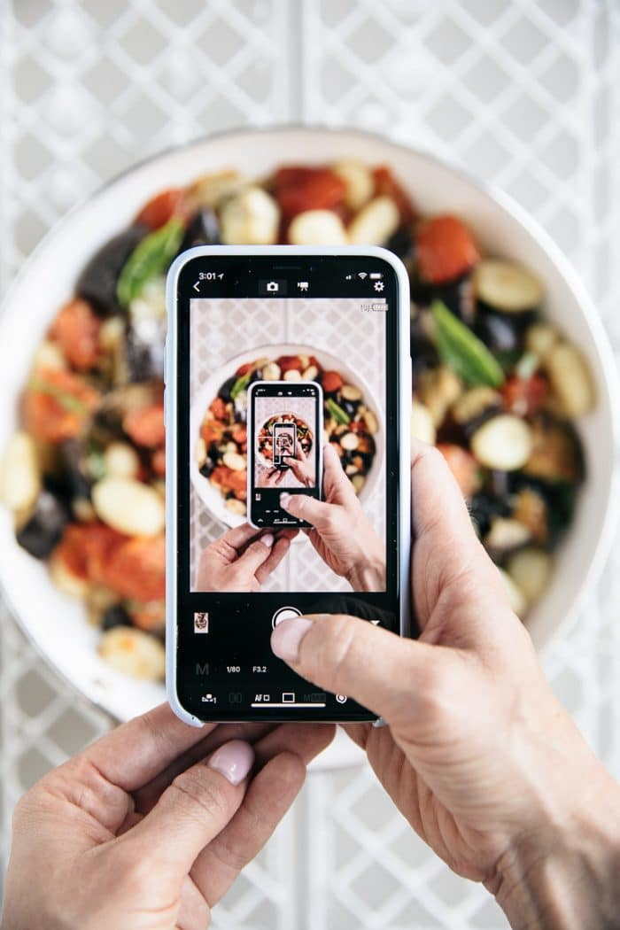Taking an image of a person taking an image of a pan filled with Roasted Eggplant and Tomato Gnocchi