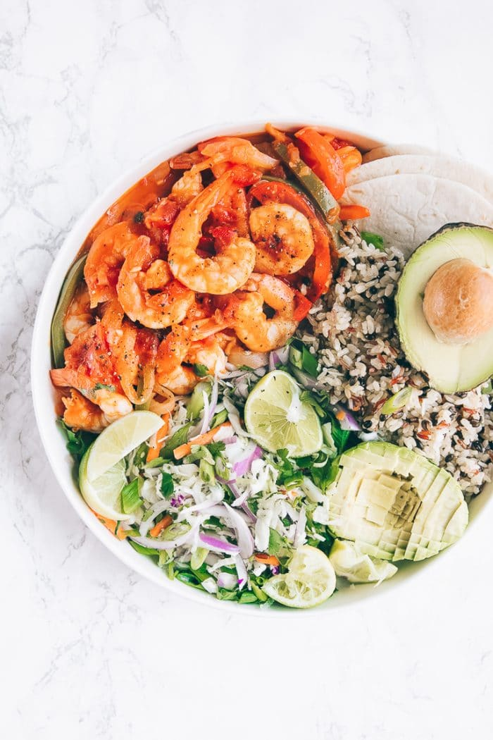 Spicy shrimp cooked in tomatoes with bell pepper and served with rice, salad, and avocado