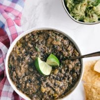 White bowl filled with refried black beans and set on a table with guacamole and tortilla chips.