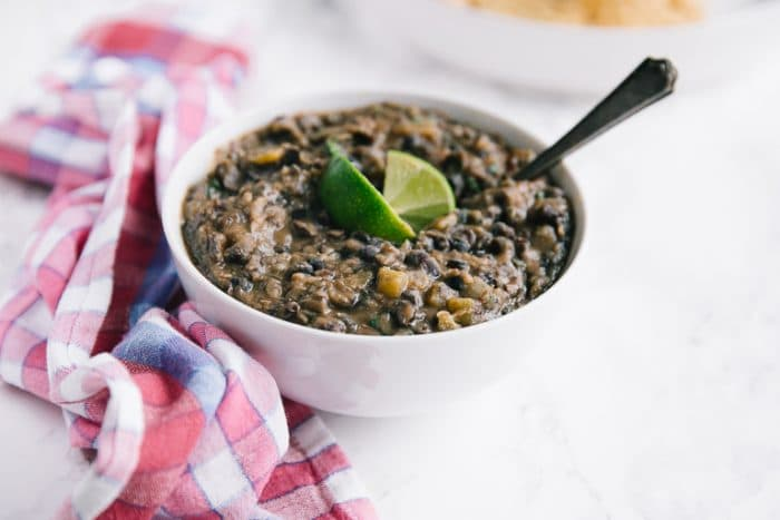 Large white bowl filled with homemade refried black beans.