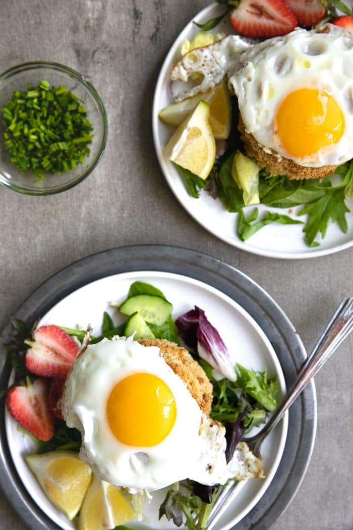 Two plates with fresh greens, salmon crab cakes, and fried egg