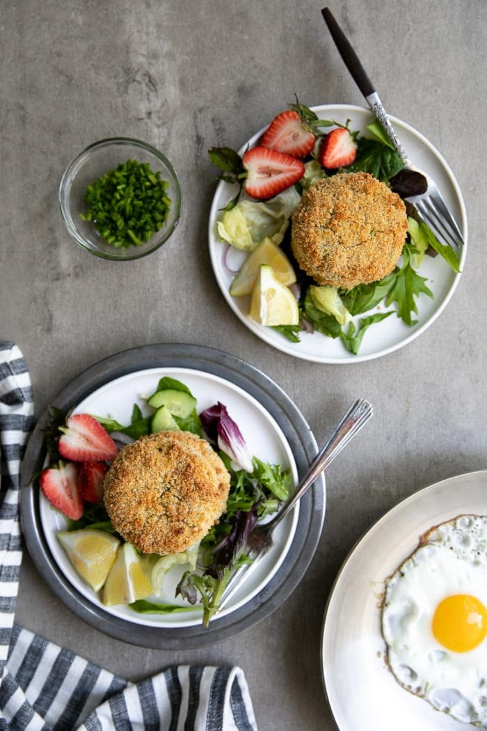 plated salmon crab cakes on a bed of lettuce and side of strawberries