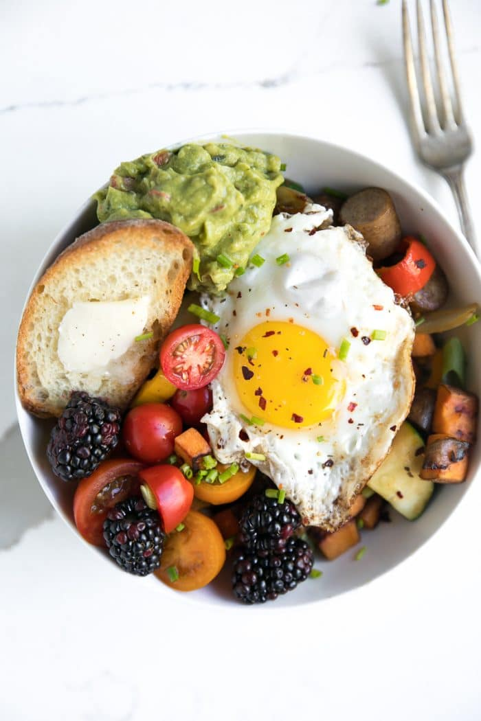 Sweet Pepper and Sausage Breakfast Hash with egg, guacamole, tomato, and sweet potato