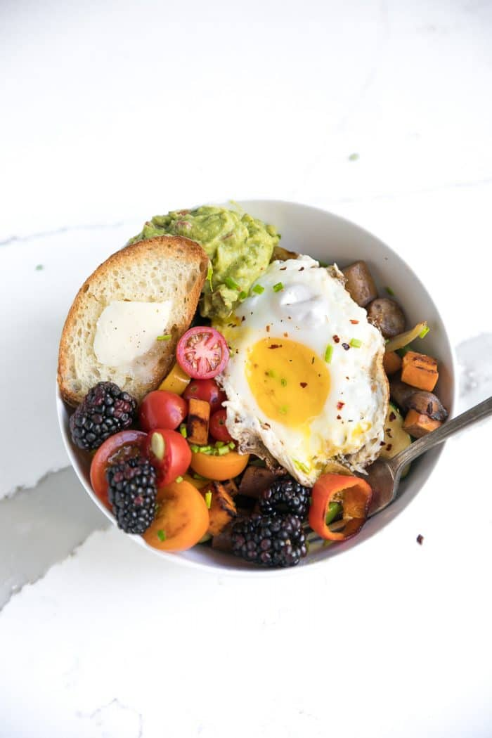 Breakfast hash bowl with egg on top and a broken yolk