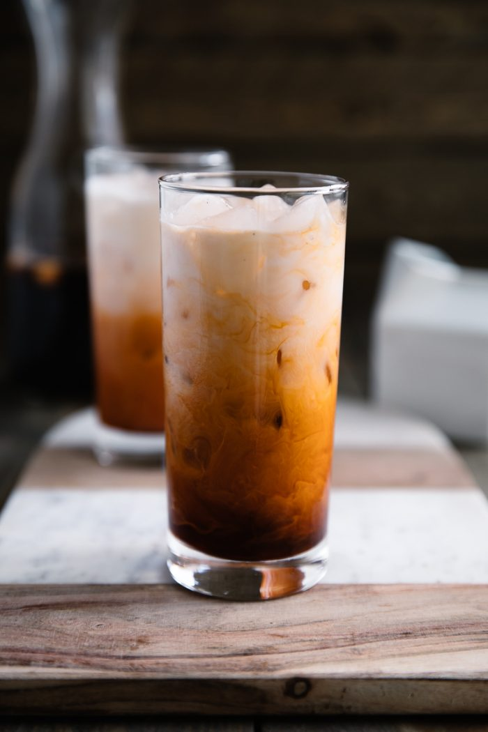 Thai iced tea in a glass mixing with cream