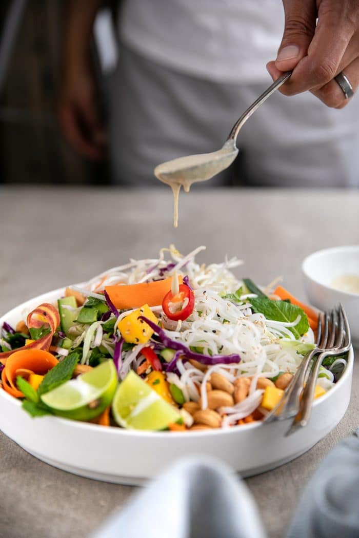 Drizzling creamy peanut butter dressing over Thai noodle salad