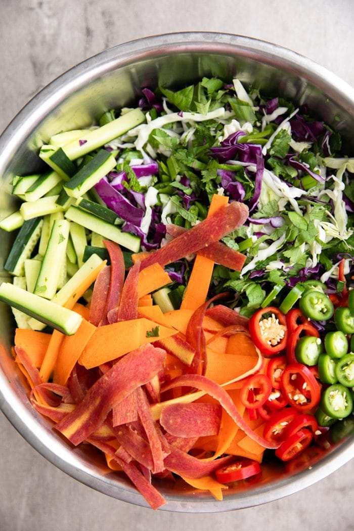 Mixing bowl filled with fresh chopped greens, herbs carrot ribbons, and cucumber.