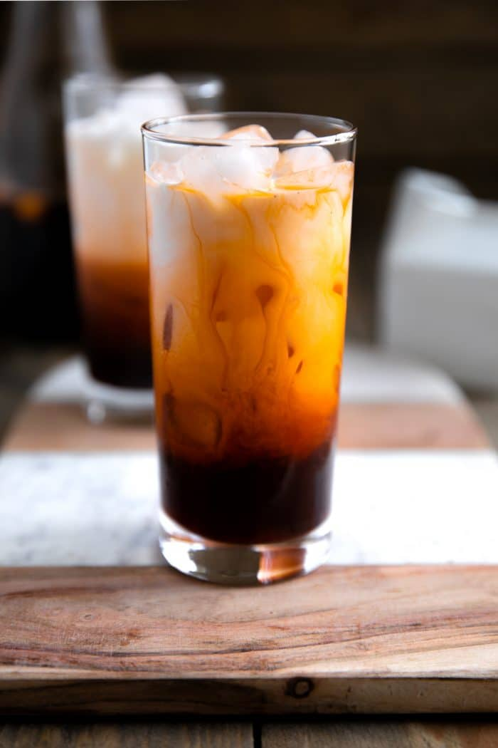 Glass filled with ice, tea mix, and condensed milk.