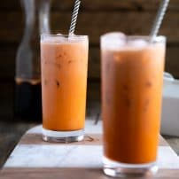 Two glasses filled with prepared and iced Thai iced tea.