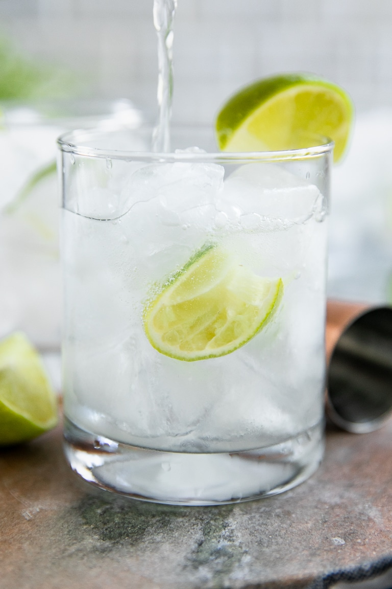 Filling a gin and tonic with tonic water