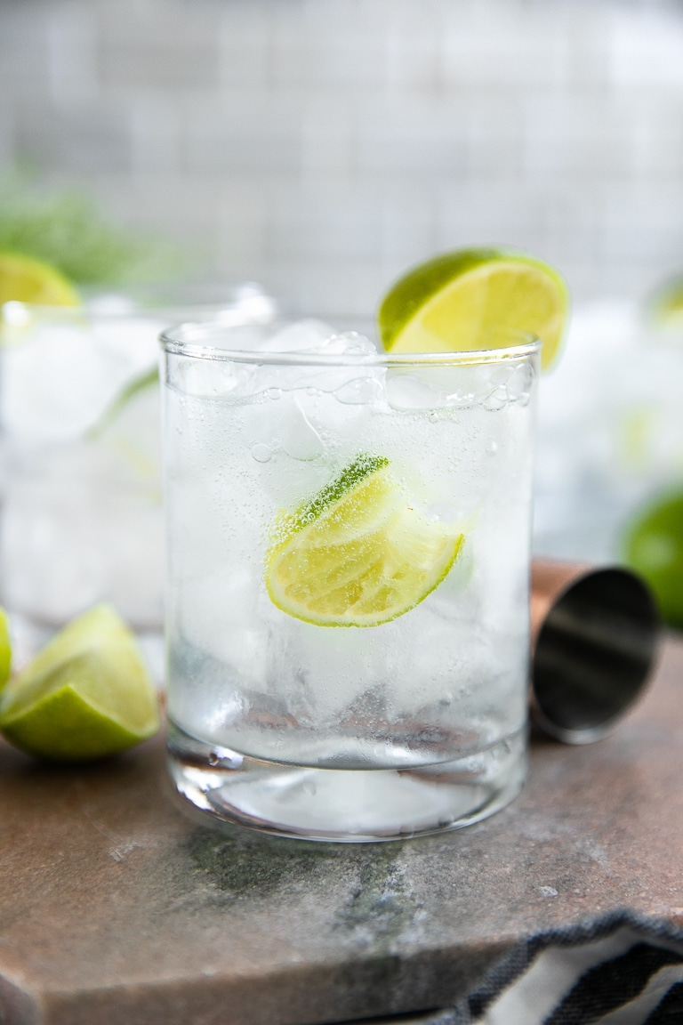 Classic gin and tonic in a highball glass with two limes