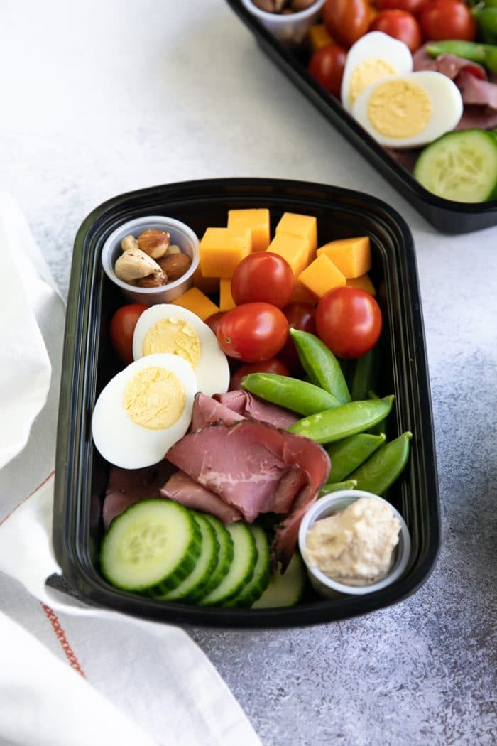 lunch meal prep tray with cheese, nuts, cherry tomatoes, sugar snap peas, cucumber, hummus, deli meat, and hardboiled egg