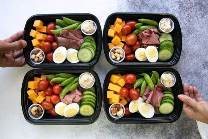 four meal prep lunch trays containing high protein snack foods