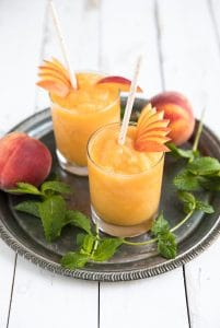 Wine slushies made with frozen peaches and white wine served in high ball glasses.