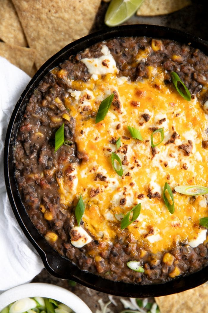 Close up image of hot black bean dip with melted cheese in a skillet