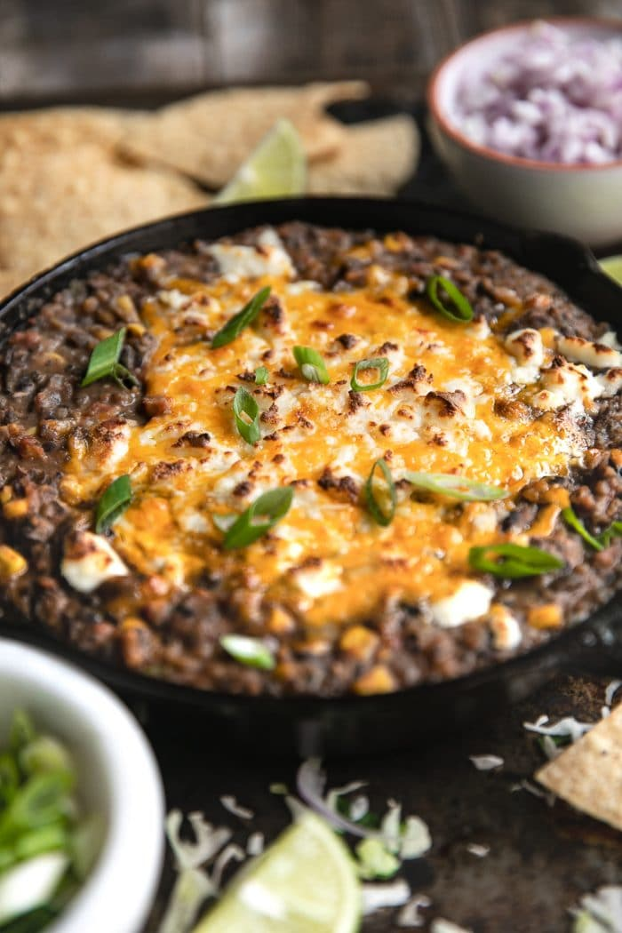 Hot and melted cheese covering skillet filled with black bean dip