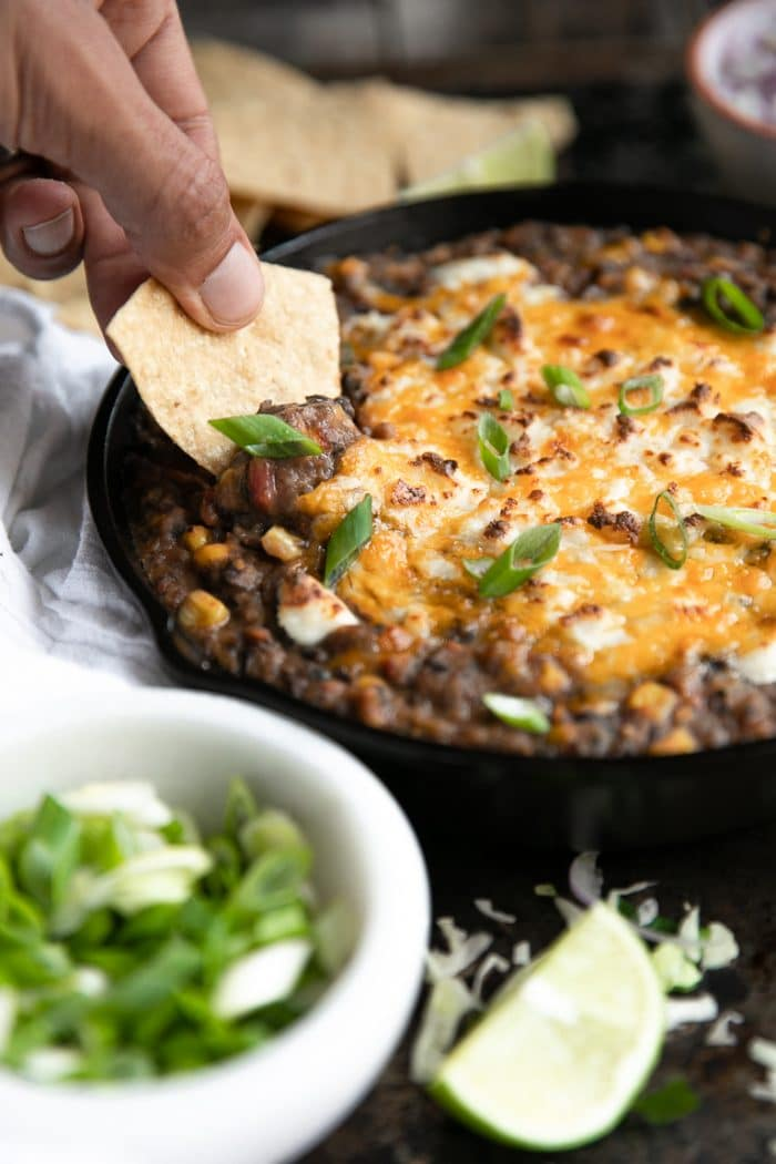 Man using a chip to scoop black bean dip with cheese