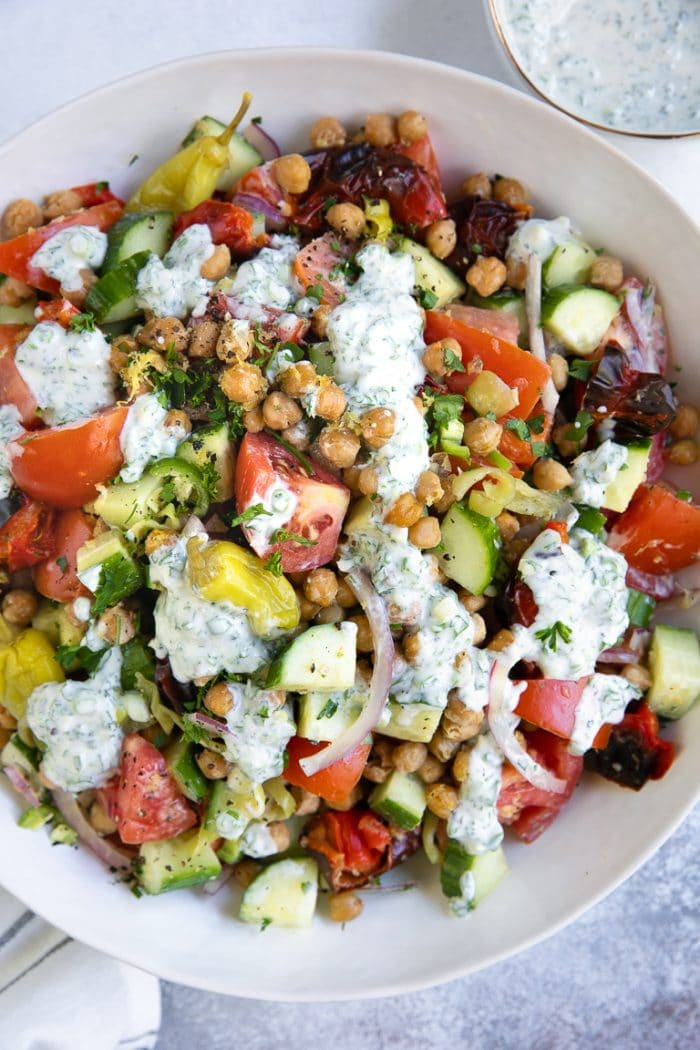 Big bowl of mixed roasted chickpea tomato salad with herbed yogurt dressing