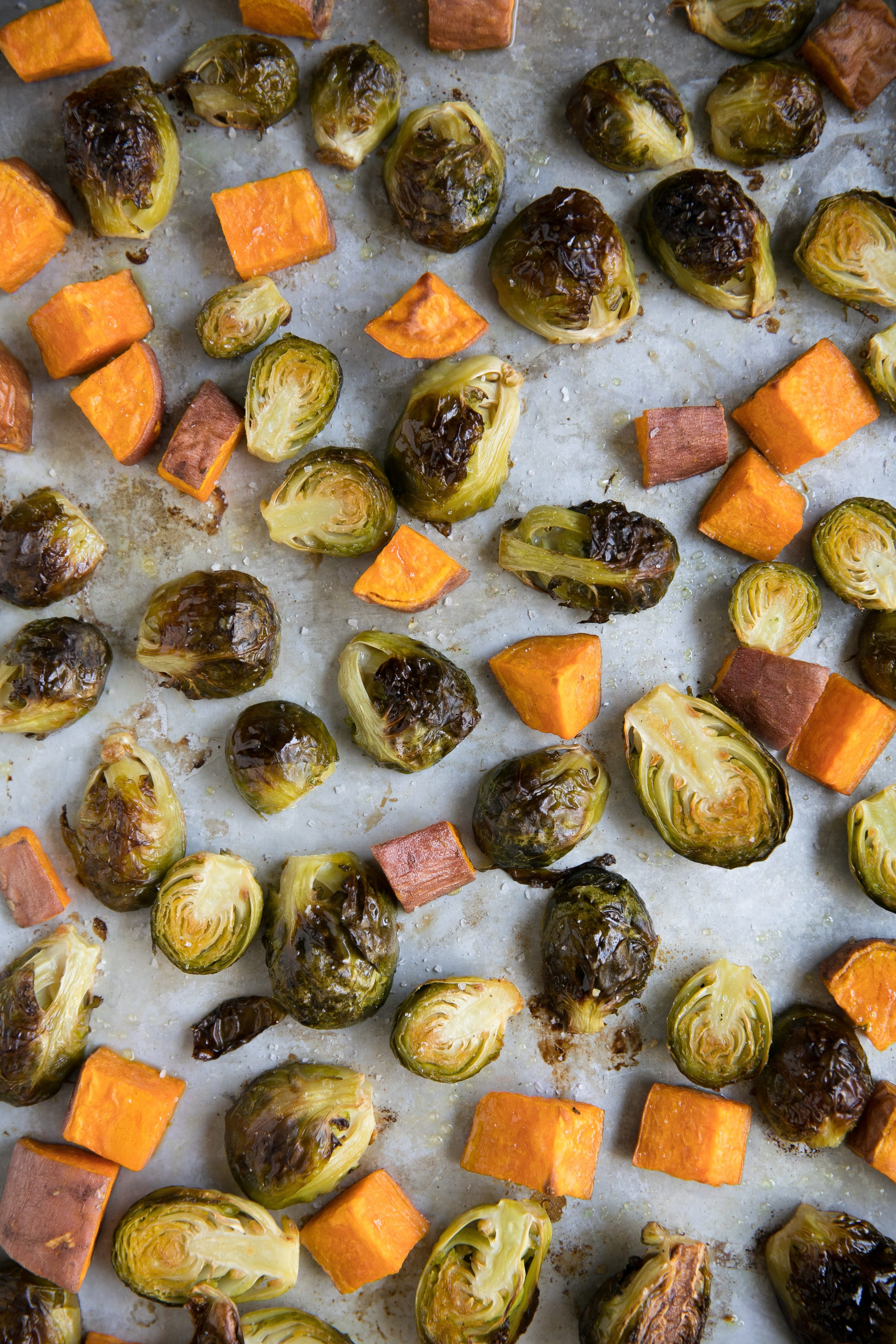 Roasted crispy Brussels sprouts and cubes of sweet potatoes on a large baking sheet.