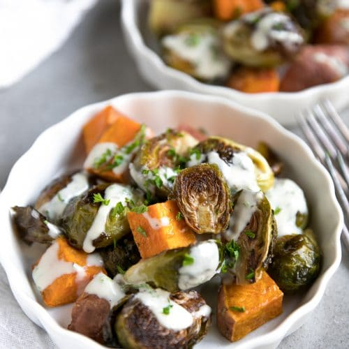 Small white plates filled with individual servings of oven-roasted Brussels sprouts and sweet potato cubes drizzled with tahini and chopped parsley.