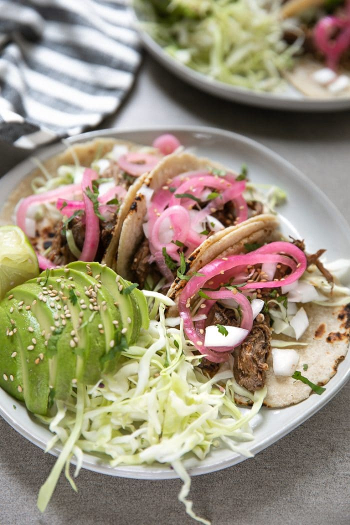 Shredded Beef Tacos with cabbage, pickled red onion, avocado, sesame seeds, and onion