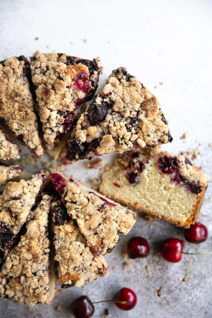 overhead shot of a sliced cherry cake with crumb topping