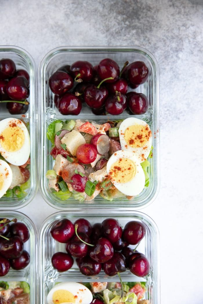Easy meal prep tray filled with chicken potato salad, hard boiled egg and fresh seasonal fruit.
