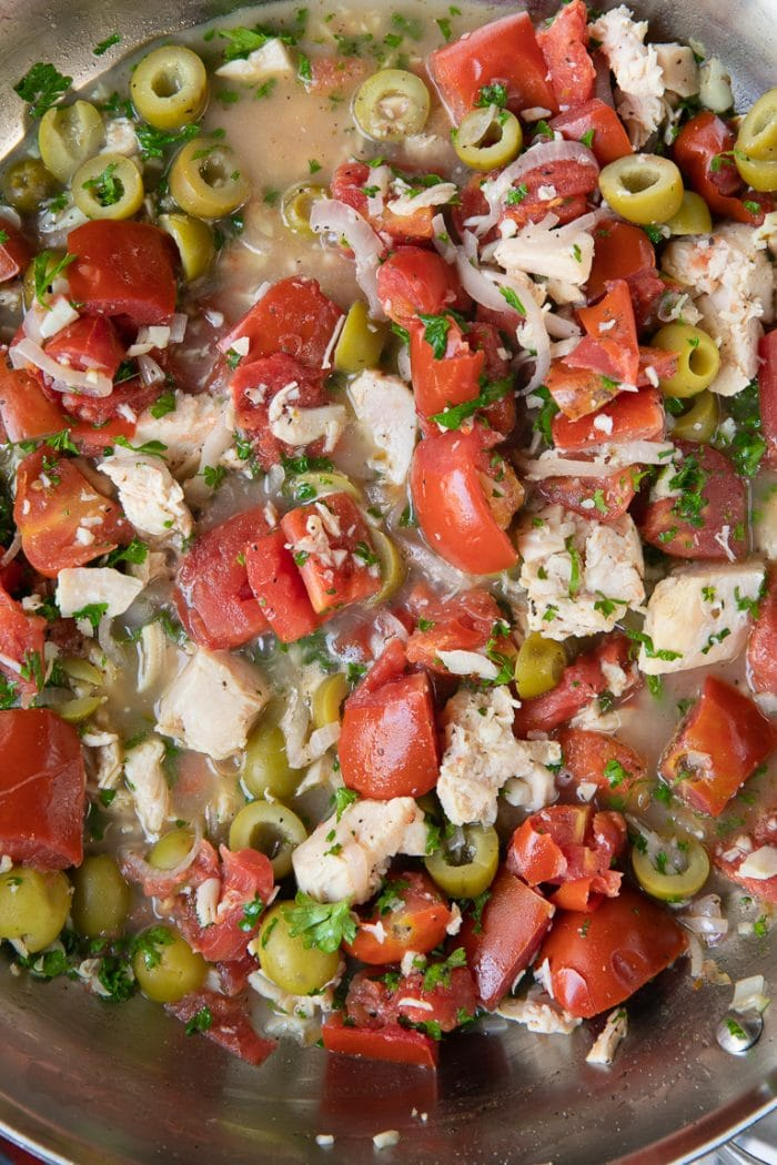 Close-up image of tomatoes, green olives, and chicken cooking together in a large skillet