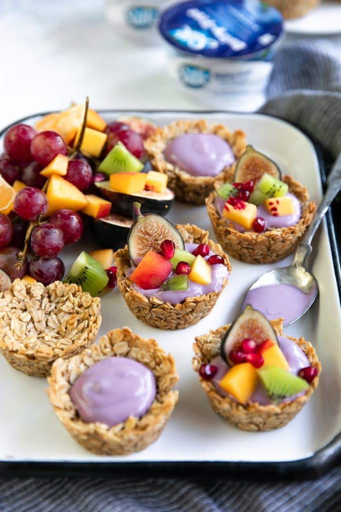 Prepared baked oatmeal cups topped with blueberry dairy-free yogurt and topped with peaches, kiwi, pomegranate, and figs.