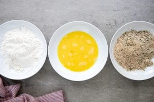A bowl of food on plates with flour, egg, and breadcrumbs
