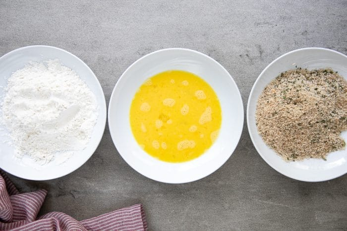 Bowls filled with flour, egg wash, and Panko breadcrumbs for popcorn chicken