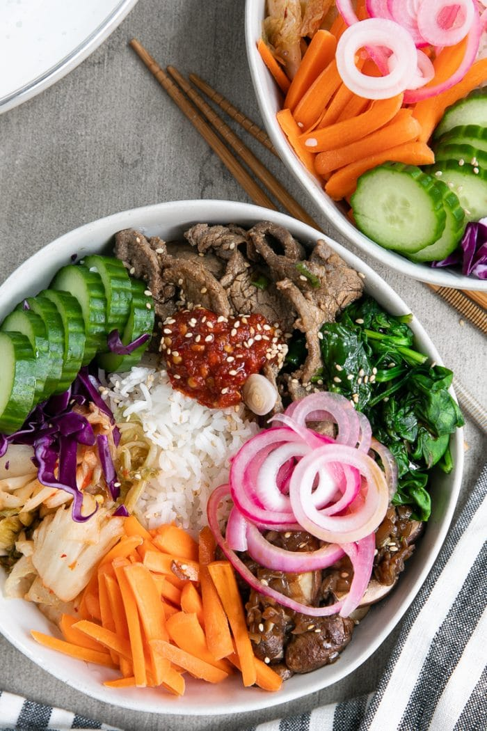 bibimbap topped with bulgogi, cooked spinach, kimchi, carrots, cucumber, sauteed mushrooms and pickled red onion.