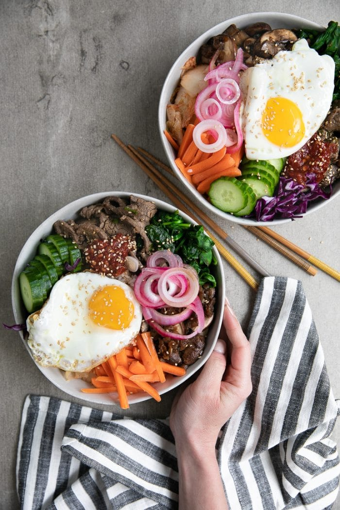 bibimbap topped with korean beef, fresh vegetables, korean chili paste, sauteed vegetables, and fried egg.