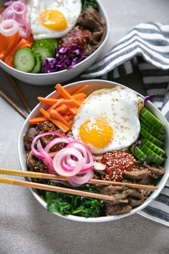 Easy bibimbap recipe with korean beef, cooked spinach, cooked mushrooms, and fried egg on top.