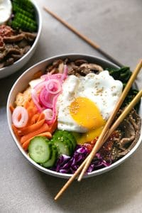 A bowl of food on a plate, with Beef and Bibimbap