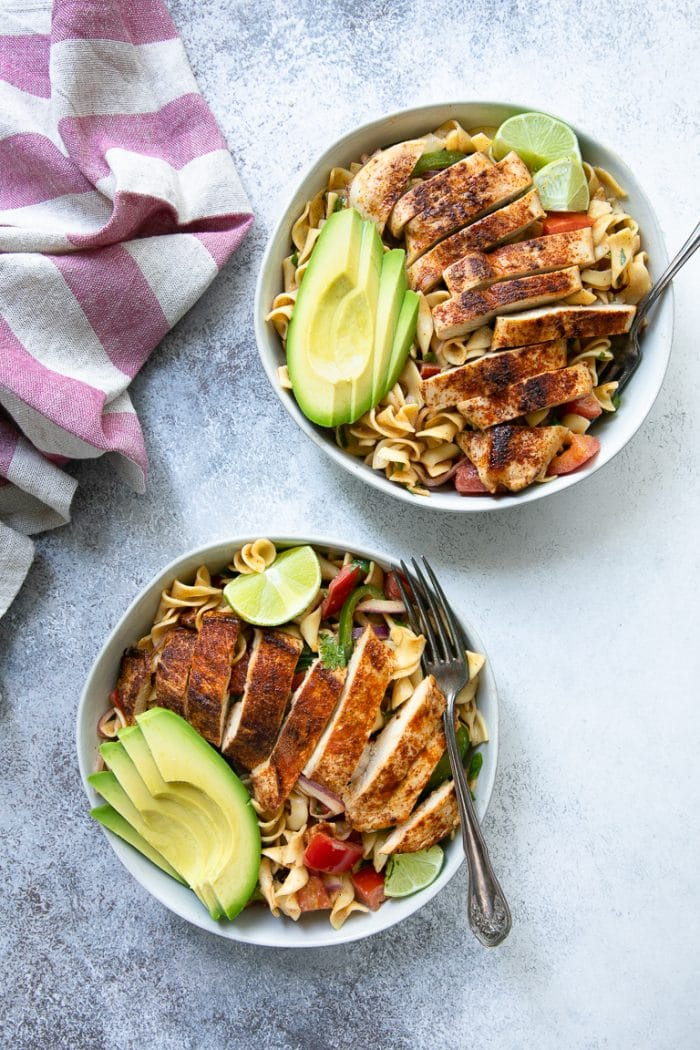 Two bowls filled with Cajun Pasta Salad with avocado and Cajun Baked Chicken
