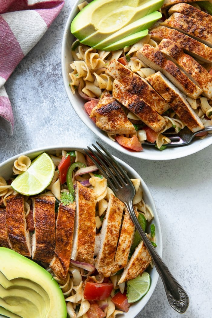 Overhead close-up images of two bowls filled with creamy cajun noodles, vegetables and chicken.