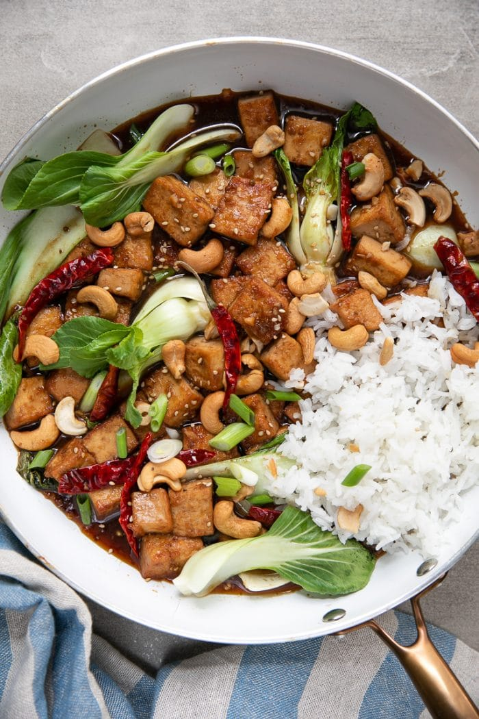 Skillet filled with bok choy, tofu, and rice all mixed together in a sweet and spicy orange marmalade sauce.