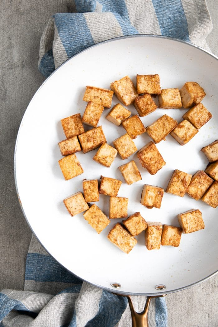 Browned tofu cubes in a white skillet.
