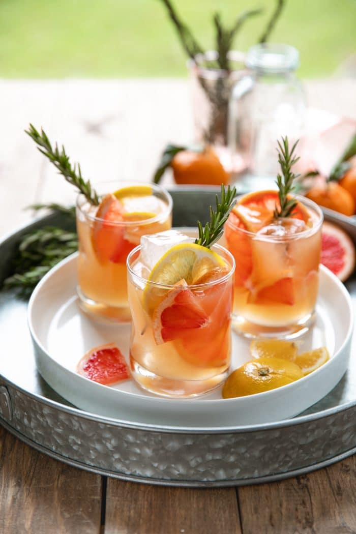 Tray with three glasses filled with Bourbon and grapefruit cocktail with rosemary