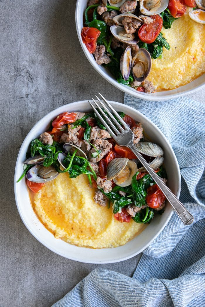 Overhead shot of two large white bowls filled with polenta, cooked clams in white wine, spinach, and Italian sausage