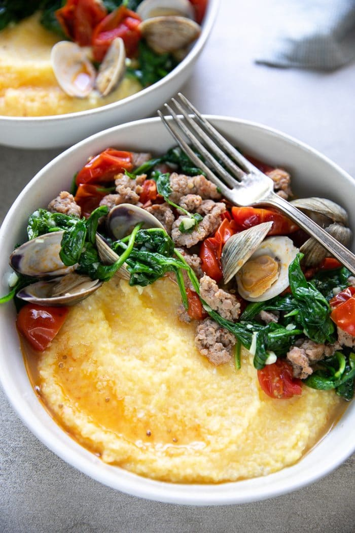 Cooked littleneck clams in white wine sauce with burst cherry tomatoes, spinach, Italian sausage all on top of creamy polenta.
