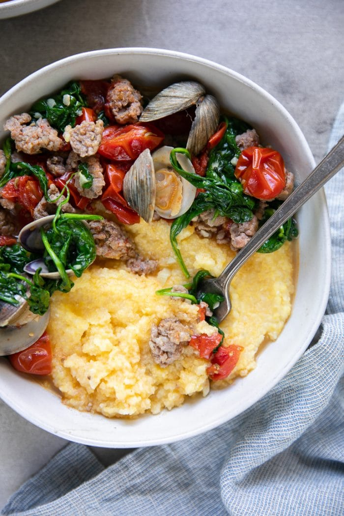 overhead image of a bowl with a fork scooping up polenta and sausage and drunken clams