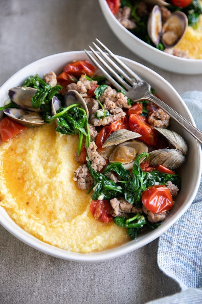 Littleneck clams, spinach, cherry tomatoes, and sausage piled on top of cooked polenta ready to be eaten